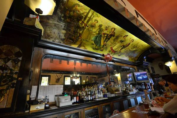 A 1906 mural of a beer picnic created by the Milwaukee Artists' Association graces the ceiling above the bar at Michigan House Café, home of Red Jacket Brewing in Calumet, MI.