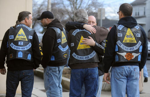 (Center, face showing) Andy Williams, a Last Chance Motorcycle Club member and brother-in-law of Keith Michaelson, hugs another club member after the sentencing of John P. Heaney III at the Northampton County Courthouse on Monday on involuntary manslaughter for a fiery wreck that killed two motorcyclists in Bangor.
