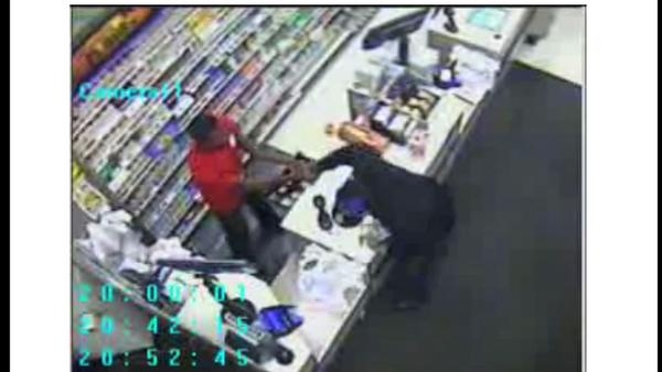 Freeze-frame from surveillance video showing gloved man snatching cash from a Walgreens cash register.