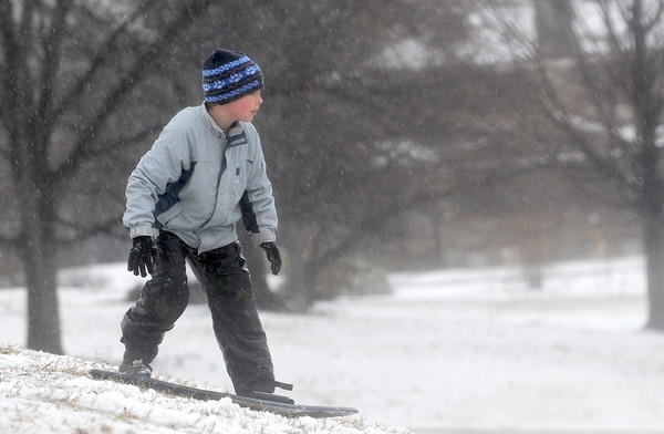 Josh Forrest, almost 9, stands on his sled at he slides down a hill at Patterson Park after about an inch of snow fell Dec. 26.