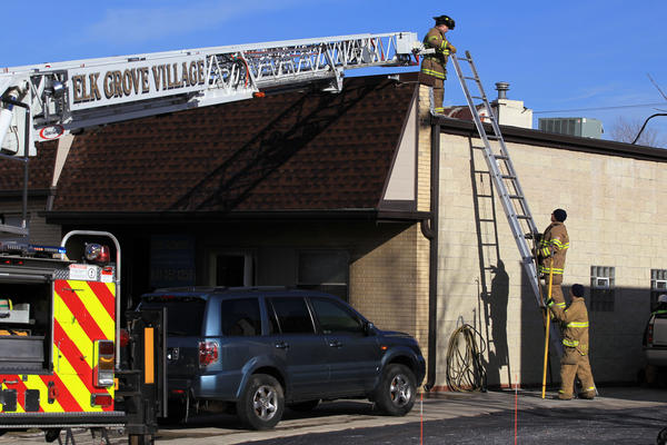 Firefighters finish up at the scene of a structure fire in the 100 block of Gaylord in Elk Grove Village on Monday. Several cars burned up in the fire at Quality Automotive.