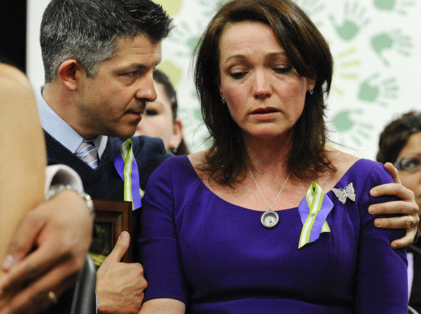 Ian and Nicole Hockley, parents of Sandy Hook school shooting victim Dylan, listen at a news conference at Edmond Town Hall in Newtown, Conn., on the one-month anniversary of the massacre.