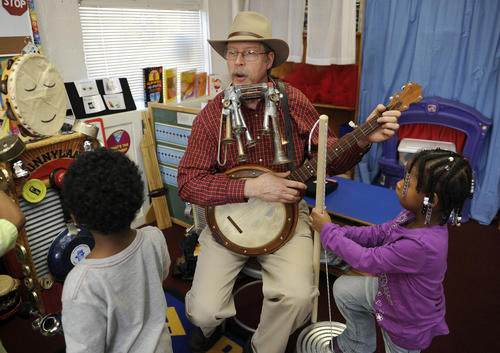 Slim Harrison, artist in residence at the Harriet Tubman Head Start Center, in Columbia, plays folk music with a class of children.