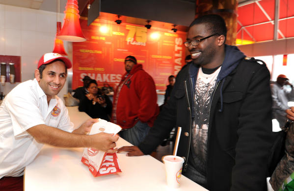 "Peter Tabibian, co-founder and CEO, left, gives a free burger to Mayo Omolabi, 23, from Middle River. Z-Burger on The Avenue kept their promise that if the Ravens won against Denver Broncos, Z-Burger would give out free burgers Sunday to everyone who said, ""Super Bowl,"" when they ordered."