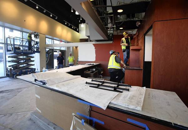 Sub-contractors for Turner Construction install mounts for Flat Screen televisions inside a unnamed restaurant at the Amway Center in downtown Orlando.