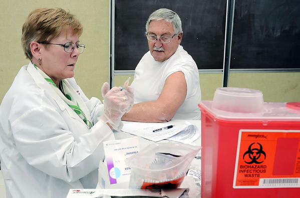 Community Health Nurse Patti Murphy prepares a flu shot for Billy Snoots on Monday at the Washington County Health Department.