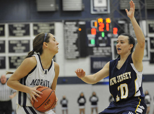 Moravian's Katie O'Rourke attempts to pass around New Jersey's Kylie O'Donnell. The Moravian College women's basketball team played against The College of New Jersey Monday January 14th, 2013 at Johnston Hall on the campus of Moravian College in Bethlehem.