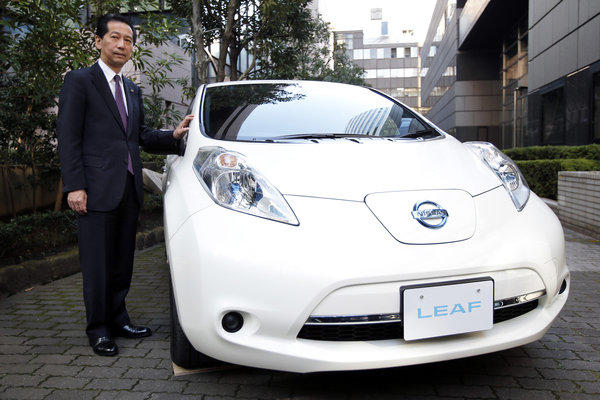 Masaaki Nishizawa, senior vice president of Nissan Motor Co., stands alongside the updated Nissan Leaf electric vehicle. Nissan introduced a cheaper version of the electric vehicle to lure cost-conscious buyers as sales of the original model have fallen short of the company's target.