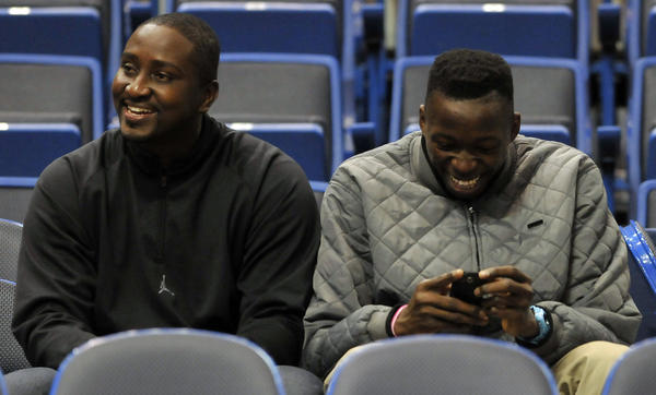 Recruit Amidah Brimah, right, sits with his guardian, Nana Baffi at UConn's game against Louisville Monday night. Brimah has committed to playing at UConn.