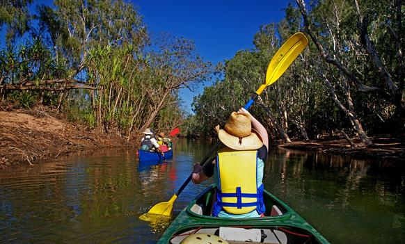Canoeing on the Katherine River, which flows through Arnhem Land and Kakadu National Park. The river runs through the 13 flaming red-walled gorges that make up the Katherine Gorge of Nitmiluk Park, and past the namesake town of Katherine.