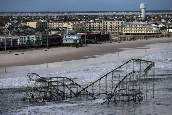 Waves break over a roller coaster wrecked by Superstorm Sandy last year on the East Coast.