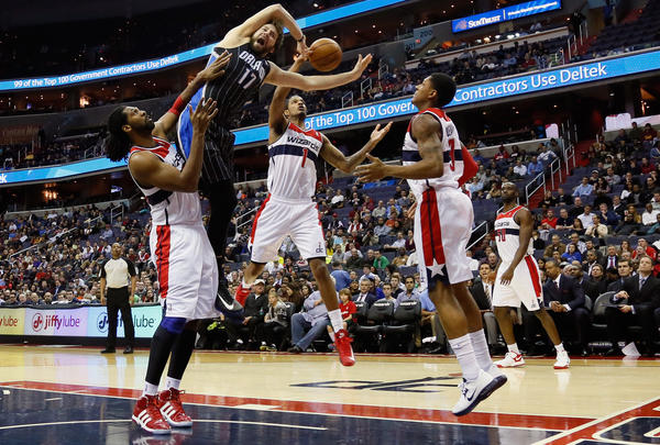 Trevor Ariza #1 of the Washington Wizards blocks a shot by Josh McRoberts #17 of the Orlando Magic as Nena #42 (L) and Bradley Beal #3 of the Wizards look on during the first half.