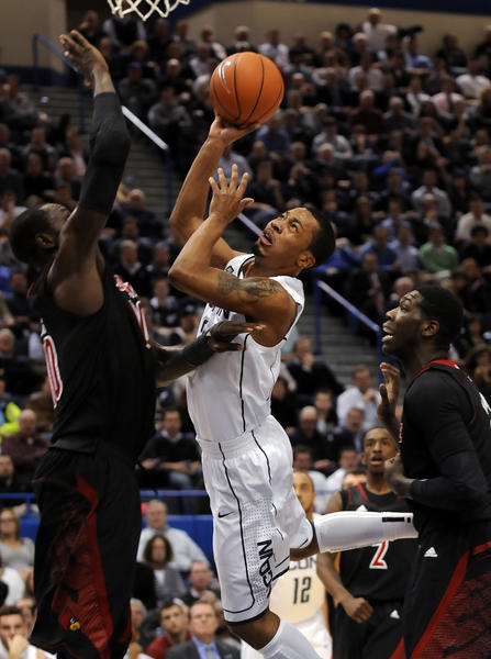 UConn guard Omar Calhoun, who scored 20 points, drives against Louisville Cardinals center Gorgui Dieng, left, and forward Montrezl Harrell Monday night at the XL Center, but the Huskies faded down the stretch in a 73-58 loss.