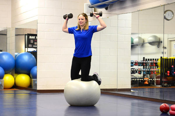 At West End 24/7 Fitness Club personal trainer Jenn Belch demonstrates the kneeling on the stability ball with dumbell overhead press exercise. Balance core training combines strength exercises with acrobatics on an exercise ball to produce a very balanced exercise routine..