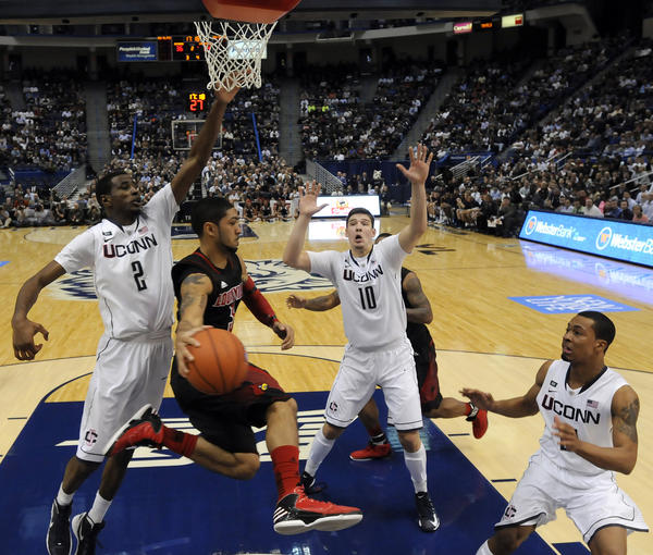 Louisville Cardinals guard Peyton Siva drives past UConn forward DeAndre Daniels, left, before dishing off in front of UConn forward Tyler Olander (10) and guard Omar Calhoun during the second half Monday night at the XL Center. Siva scored 11 points and had 4 assists in a 73-58 Louisville victory. Daniels (2) scored 9 points and grabbed 5 rebounds while Calhoun (R) scored 20 points but had 6 turnovers on the night.
