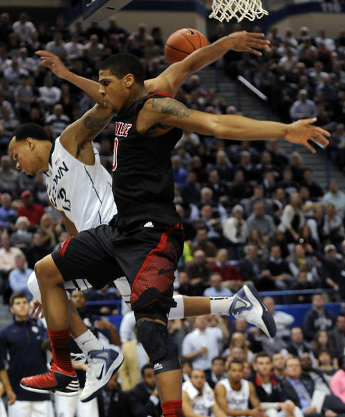 UConn guard Shabazz Napier, left, gets fouled by Louisville Cardinals center Gorgui Dieng during the second half Monday night at the XL Center. Napier scored 12 points and handed out 6 assists in a 73-58 loss.