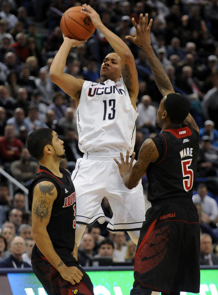 UConn guard Shabazz Napier takes a desperation shot against Louisville Cardinals guard Peyton Siva, left, and guard Kevin Ware as the shot clock expires in the second half Monday night at the XL Center.