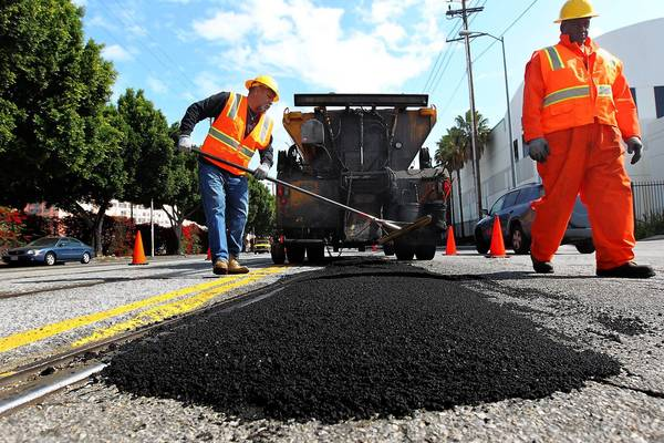 There is a fear at L.A. City Hall that the pool of money available for road work is about to shrink dramatically. Above, workers fill a pothole in 2011.