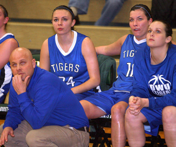 Dakota Wesleyan's Brittany Hills (24), of Summit, and Elizabeth Lamb (10), of Onida, watch the action from the bench along with their coach Jason Christensen, lower left, last season during a game at Presentation College. American News File Photo by John Davis