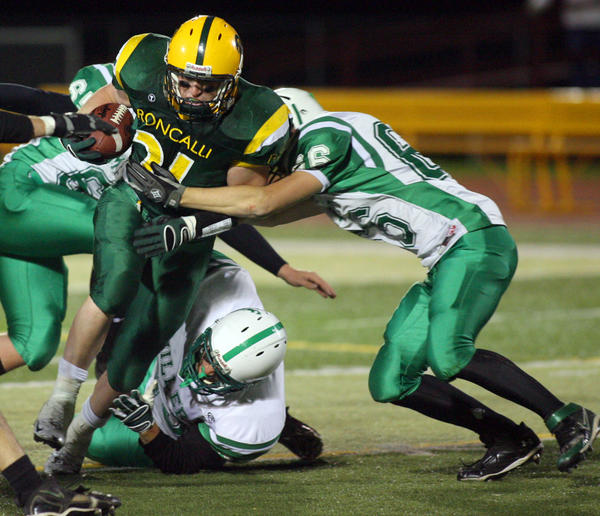 Aberdeen Roncalli's Brendon Hoellein, left, tries to run through the tackle of Miller¿s Mikey Roy, right, a game at Swisher Field in 2010. Hoellein is transferring to play football for Northern State after playing baseball for a year at Augustana College. American News File Photo by John Davis