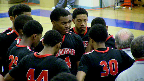 Westchester basketball team surrounds Coach Ed Azzam during game against Palisades.