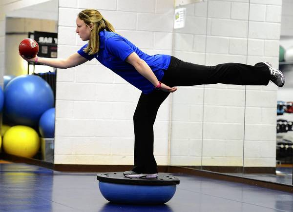 Personal trainer Jenn Belch demonstrates a one-legged balance on a Bosu ball. She promotes core training that combines strength exercises with acrobatics on an exercise ball.