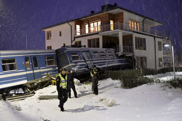 Police officers stand around a local train that derailed and crashed into a residential building in Saltsjobaden outside Stockholm in this picture taken by Scanpix Sweden January 15, 2013. According to local media, a spokesman from Arriva, the company that operates the train line, says the train was stolen by a domestic cleaner,  who stole the train for unknown reasons. The cleaner was taken to a hospital after the crash. No residents in the building were injured.