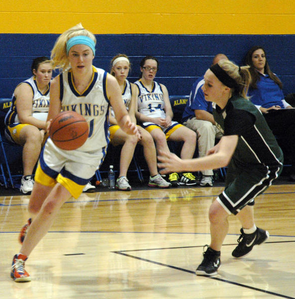 Alanson's Alenna Kilpatrick (left) looks to drive on a Kinross Maplewood Baptist player Monday at the Alanson High School gym.