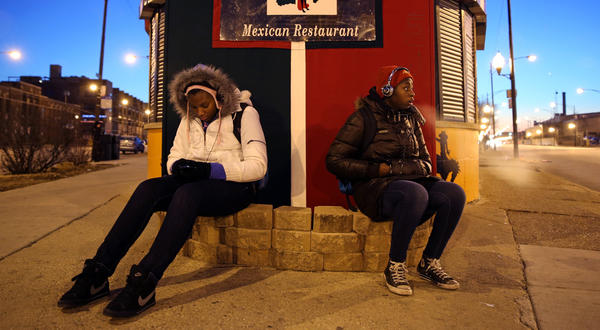Jasmine Syse, 17, left, and her sister Janette, 16, wait for the 65 Grand bus at the corner of Grand and Chicago Ave. to take them to Prosser Career Academy today. The temperature was about 15 degrees during their wait.