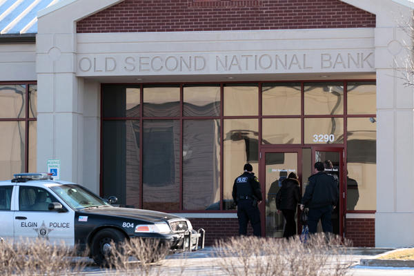 Elgin Police officers investigate a bank robbery at Old Second National Bank in Elgin on Tuesday.