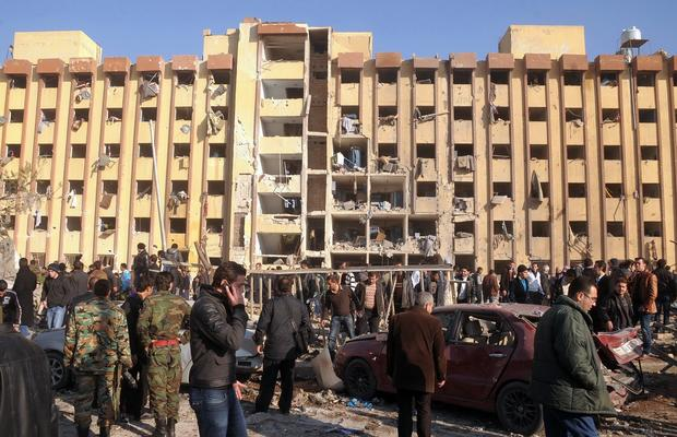 Syrians gather in front of a building damaged by an explosion at Aleppo University.