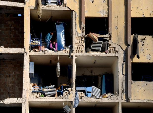 Syrians look down from a building whose rooms were exposed when an explosion sheared off part of an exterior wall at Aleppo University.