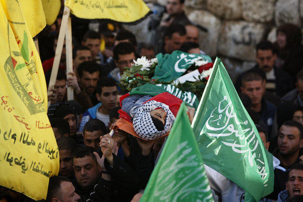 Palestinians carry the body of the 17-year-old Samir Awad during his funeral in the West Bank village of Budrus on Tuesday.
