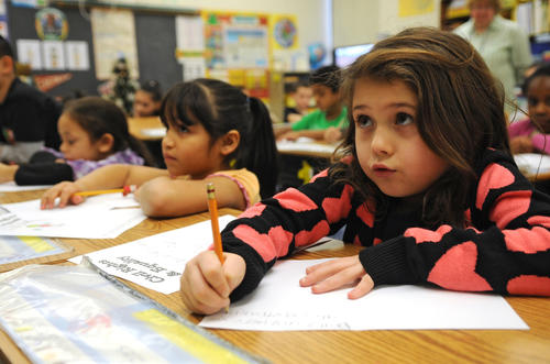 1st grader Manaira Fernandes looks up at the board while she writes a letter to children of military service members. Easton School district held their Day of Service Tuesday. At Paxinosa Elementary the high school Key Club came down and read the children a story about Dr. Martin Luther King Jr. and did exercises with them to help them understand what King was fighting for.  They also wrote cards to children of military service members.
