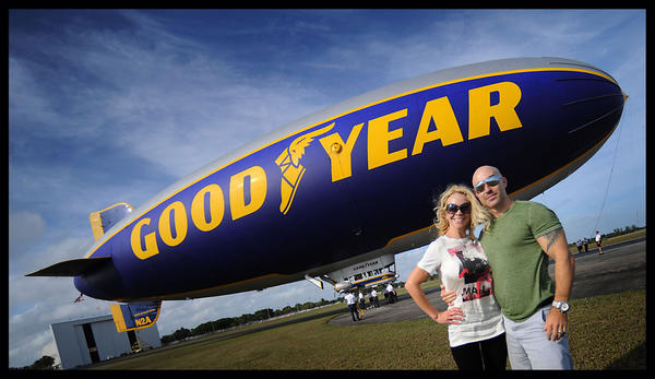The Goodyear Blimp, The Spirit of Innovation, sits on it's landing spot as passengers Erica Thaler and friend Erik Cavanagh pose for a quick photo after their hour-long ride.  Erica won the ride through a charity.    When the blimp is not covering major sporting events, it raises money for charities by auctioning off rides through various charities.
