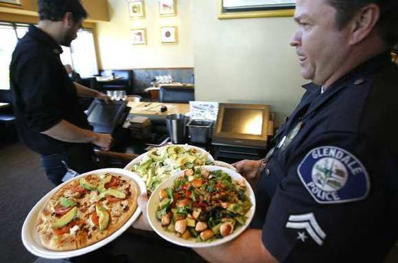 Once a waiter, Glendale Police officer Joe Allen carries four plates of food, three balanced on one arm, to a table at the California Pizza Kitchen in Glendale Tuesday, Jan. 15, 2013.