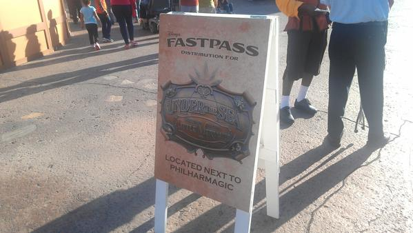 Signs direct Magic Kingdom guests to the FastPass distribution location for the Under the Sea attraction.