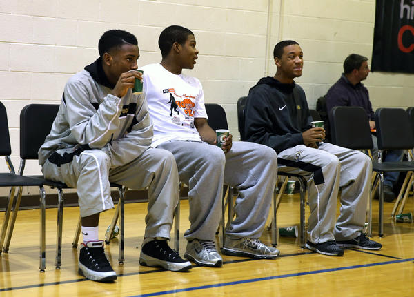 Donte Ingram, Jaycee Hillsman and Sean Moore (left to right) sit on the sidelines in street clothes before Simeon Career Academy hosted Chicago Vocational Monday in a public league basketball game. The three were declared ineligible to play by the IHSA Tuesday, because of residency issues.