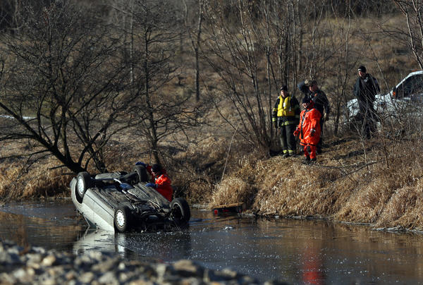 Emergency workers investigate the scene where a car landed in a creek south of Route 30 in Plainfield, Ill. A person was found dead inside the car.