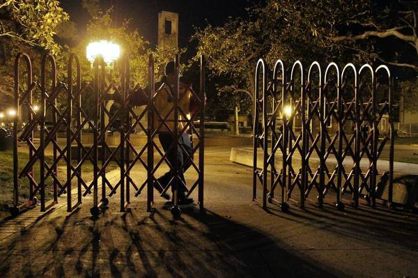 A guard closes a portable gate at USC under the new security precautions.