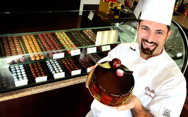 Chef Alan Pitotti shows one of his creations, a chocolate cake called the Dolce. Behind him are some of his hand-colored chocolates. Pitotti of Hellertown's Dolce Patisserie competes on Sweet Genius, a Food Network show, on Jan. 17.
