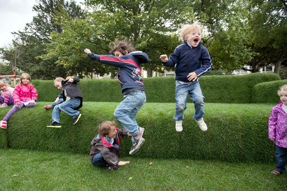Children jump on a grass-made sofa