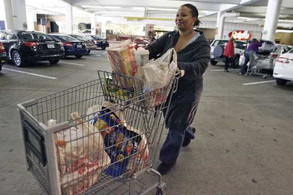 Kristine Henderson loads her car with plastic bags of groceries after shopping at Ralphs in Glendale on Tuesday.
