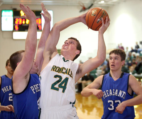 Aberdeen Roncalli's Lucas Lorenz, center, moves to the basket between Redfield-Doland's Landon Rohlfs, left and Jake Baloun, right, during Tuesday night's game at the Roncalli High School gym.