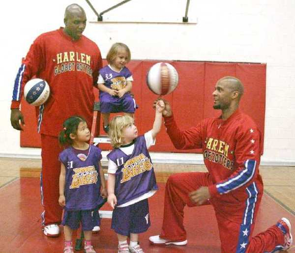 "The Harlem Globetrotters Herbert Lang, aka ""Flight Time,"" and Nate Lofton, aka ""Big Easy,"" meet children at the Burbank Community YMCA Child Development Center. They are Adara Chi, Ozzy Chichoyan and Leia Beigelat."