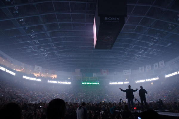 Preachers Max Lucado and Louie Giglio stand on a platform on the arena floor, while the names of the Sandy Hook shooting victims illuminate the Webster Bank Arena during a moment of silence.
