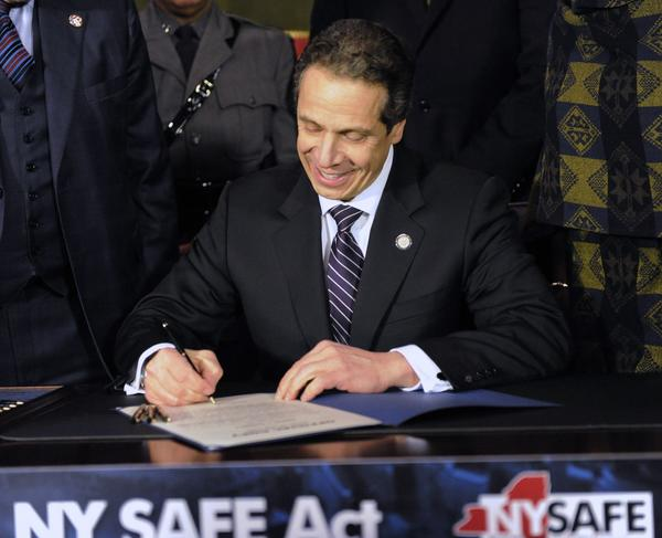 New York Governor Andrew Cuomo signs the New York Secure Ammunition and Firearms Enforcement Act at the Capitol in Albany, New York January 15, 2013. Cuomo on Tuesday signed into law one of the nation's toughest gun-control measures and the first to be enacted since the mass shooting last month at an elementary school in neighboring Connecticut.