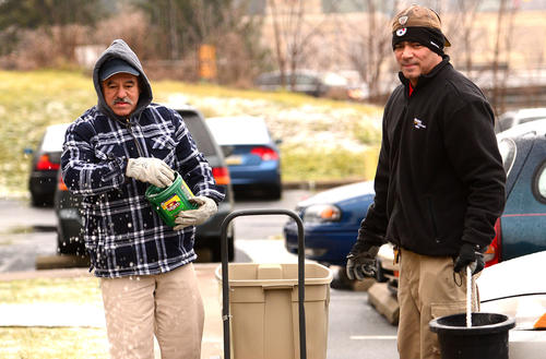 David Serrano of Allentown, left, and Raul Robles of Whitehall are in the maintenance department at Lehigh Valley Apartments on Maryland Circle and he spreads salt for residents early Wednesday as a light rain falls.