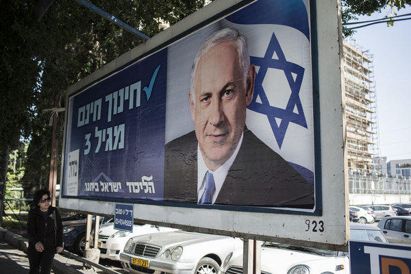 A woman passes by a campaign poster of Prime Minister Benjamin Netanyahu in Tel Aviv on Wednesday ahead of the national elections next week in Israel.