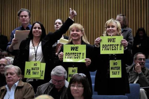 Opponents of the proposal to impose new fees on property owners to help pay for upgrades to the county's storm drain network make their feelings known at a Los Angeles County Board of Supervisors public hearing.